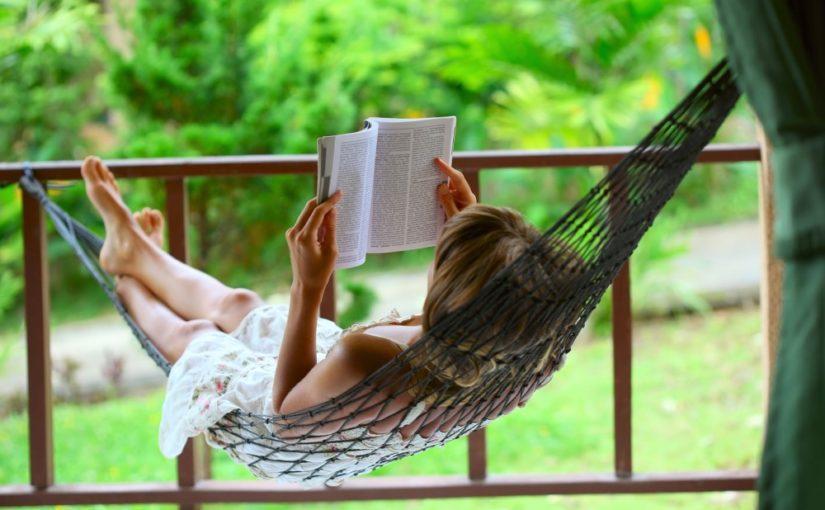 Kvinde der ligger i en hængekøje og læser