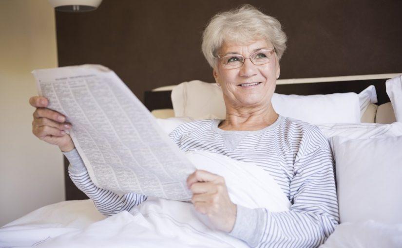Moden kvinde der læser avis i sin seng